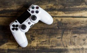 A PS4 (Playstation 4) controller on a wooden bench