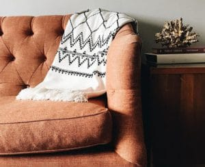 A throw strewn over a brown couch